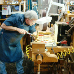 "Notice anything about this fellow?  I'll give you a hint: gray hair.  Retirement looms. ""Worker finishes the neck on a Martin guitar at the Martin Guitar factory in Nazareth, PA. - Oct 2008""  (photo by dtaw2001 - released into the public domain - thanks, dtaw2001!)"
